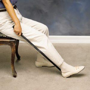 elder using long handled shoehorn